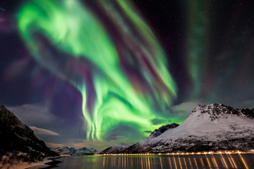 The spectacular Northern Lights unfold over a fjord, in Skjervøy, Troms, Norway. The vibrant colors are produced at various altitudes by different atmospheric gases, with blue light emitted by nitrogen and green by oxygen. Red light can be produced by both gases, while purples, pinks and yellows occur where the various colors mix and intersect.