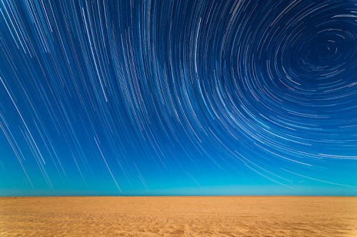 Multiple shots are compiled to create a time-lapse effect, as the Earth's rotation draws the light from the stars into long trails arcing over the beach in Mar de Ajo, Buenos Aires Province, Argentina.