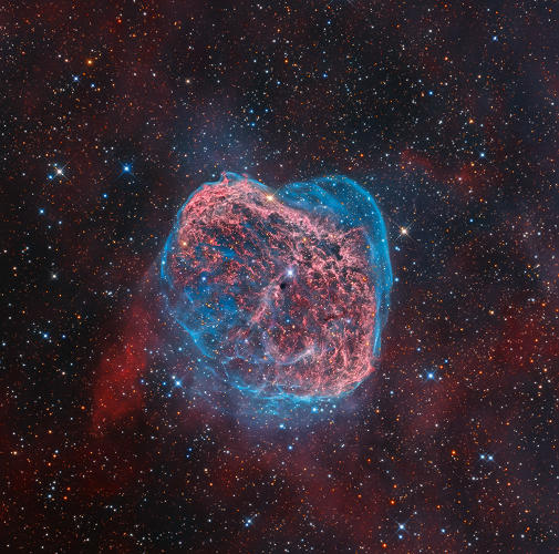 This colorful starscape, taken from Rancho Hidalgo, New Mexico, reveals the heat of the Crescent Nebula in a whirl of red and blue. The emission nebula is a colossal shell of material ejected from a powerful but short-lived Wolf-Rayet star (WR 136), seen close to the image centre. Ultraviolet radiation and stellar wind now heats the swelling cloud, causing it to glow.
