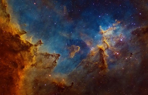 Situated 7500 light years away in the 'W'-shaped constellation of Cassiopeia, the Heart Nebula is a vast region of glowing gas, energized by a cluster of young stars at its center. The image depicts the central region, where dust clouds are being eroded and molded into rugged shapes by the searing cosmic radiation.